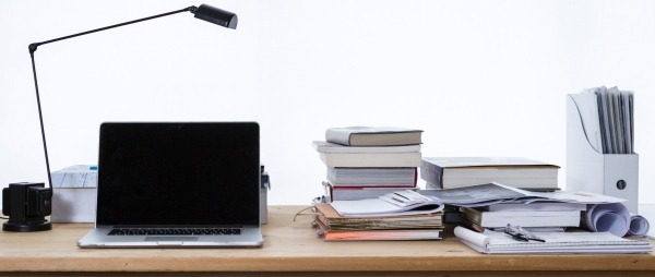 Laptop on a desk with books and other materials